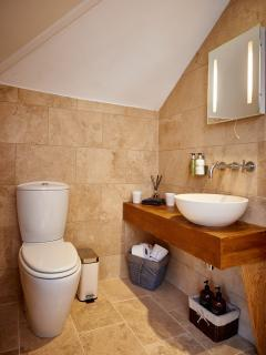The bathroom is finished in natural stone and has Molton Brown hand wash, hand cream and shower gel.