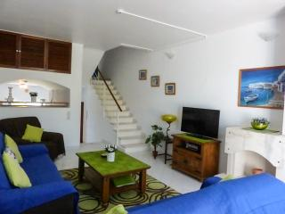 Lounge with stairs up to bathroom, bedroom and both upstairs balaconies