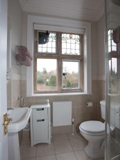 Ensuite shower room with stone mullioned window.