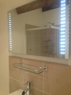 large en suite lime stone bathroom. Large shower, sink toilet LD mirrors bathroom heater.