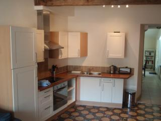 A fully equipped modern kitchen, complements the original tiled floor