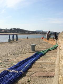 Mending nets on the harbour