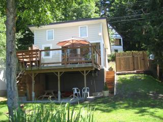 South facing facade with large deck, wooden patio furniture and a BBQ for your enjoyment.