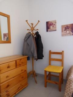 Cómoda, perchero y silla en dormitorio secundario