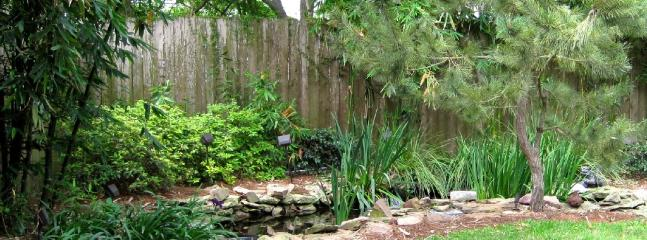 Landscaped backyard with pond.