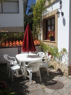 Terraza con mesa, 6 sillas y sombrilla