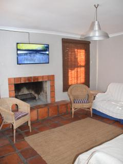 TV / living Room with fireplace & Dstv  leading to private patio with braai