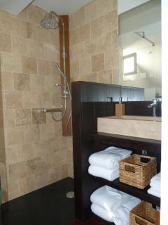 salle de bains en pierre et bois. tout le linge de toilette est a votre disposition