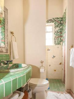 The rose and green bedrooms share a tiled bath.