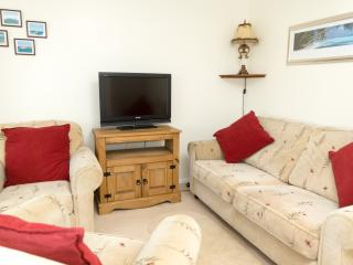 Lounge area with sofa and two armchairs and flat screen freeview TV.