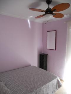 Dormitorio con cama doble , armario empotrado , ventilador de techo y balcón con tendedero;