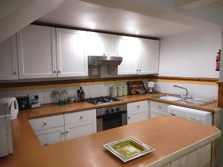 Fully equipped kitchen with microwave, oven, hob and washing machine.