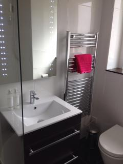 Modern bathroom with bath, electric shower, underfloor heating, heated towel rail and LED mirror