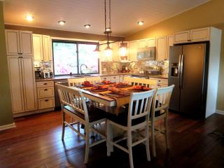 The updated spacious kitchen has quartz countertops and glass tiled backsplash.