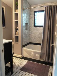The en suite bath has a marble floor & tiled tub area along with custom niche.
