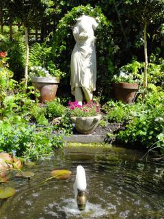 A marble venus behind a bubbling fountain.
