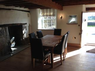 Dining room with front door open. One of two log fires. Dining table seats up to eight.