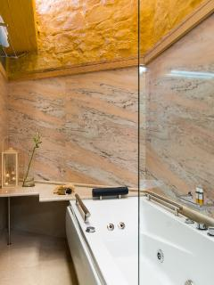 Main Bathroom with Jacuzzi bath and luxury marble surface (Rossa Portogallo)