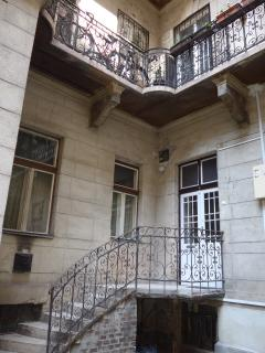 At the entrance to the mezzanine floor apartment, there is an old wrought iron staircase