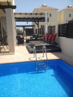 View from pool to loungers on decking to shaded area