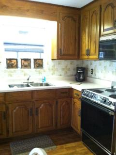 Kitchen with stove, built in microwave, refrigerator, coffee maker