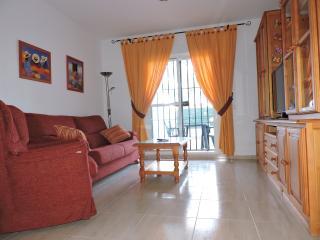 Salón con sofá de 3 plazas y sillón, mesa de comedor y 6 sillas, aparador y TV de 37'.