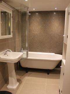 contemporary bathroom with roll top bath, rain shower and feature fossil wall