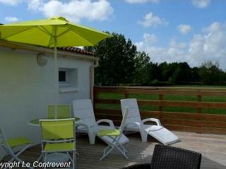 La terrasse en bois surplombe la campagne, le jardin et la piscine
