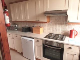 Kitchen area with cooker, fridge and microwave