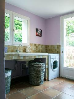 Une buanderie avec machine à laver le linge, table et fer à repasser