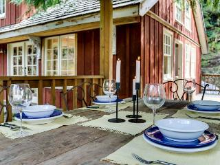 Memorable riverfront lodge with stone patio, luxe outdoor dining, & fireplace.