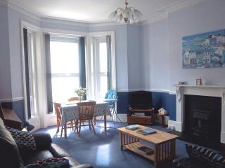High ceilings and sea view, sunny south facing sitting /dining room with relaxing reclining sofas.