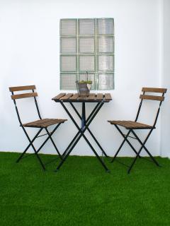 Mesa con dos sillas en la terraza superior.