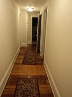 Hallway on 1st floor to 3 of its 4 bedrooms and full bath at end of hallway showing refinished floor