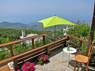 A balcony with a wooden deck for afternoon drinks looking at the magnificent view.