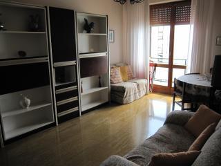Sala con accesso al balcone vista mare, con due letti singoli a scomparsa, tavolo 4posti e tv