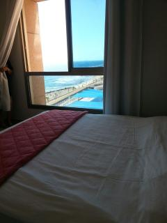 A large bedroom with a king bed and a window to the sea