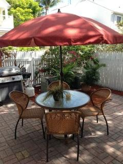 private back patio, shade, table chairs and lounges and gas grill, back gate 100 feet from pool