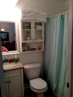 bath with tub and shower, washer dryer just outside bathroom