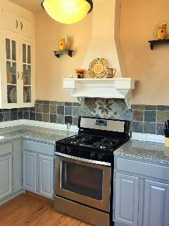 Brand new fully appointed kitchen with granite countertops and slate back splash