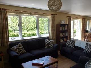 Open plan sitting room with doors to enclosed patio