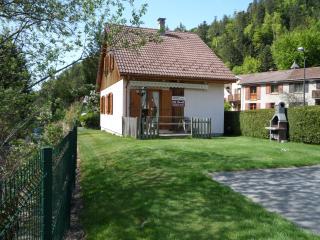vue coté terrasse bois avec table et bancs en bois store électrique sur jardin, parking, et barbecue