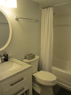 Newly remodeled ceramic tile bath/shower with marble topped vanity in Hall Bathroom.