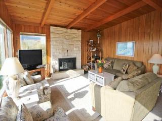Living room with cable flat screen TV/VCR/DVD, wood burning fireplace, hide-a-bed couch, loveseat, two arm chairs and large picture windows with beautiful views.