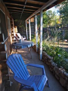 Covered porch outside the cabin with a table for outside dining.