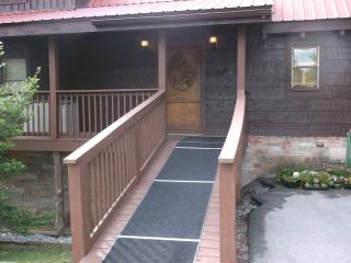 ramp going up to main door with wrap around deck on 3 sides of cabin