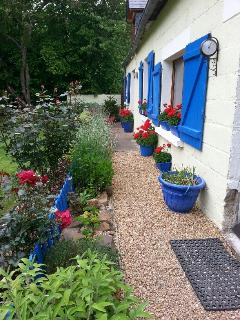 The garden is planted with seasonal flowers and shrubs with a herb garden outside the kitchen door.