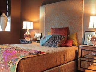 Bedroom with upholstered headboard and hand sewn coverlet
