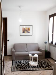 sala con divano letto // living room with sofa bed and TV