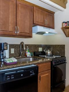 Kitchen has stove-top oven, dishwasher, microwave and coffee maker.